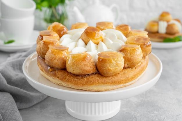 Saint honore cake with profitrols, caramel, custard and whipped cream