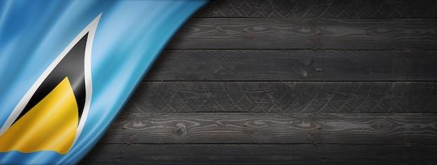 검은 나무 벽에 세인트 루시아 플래그입니다. 파노라마.