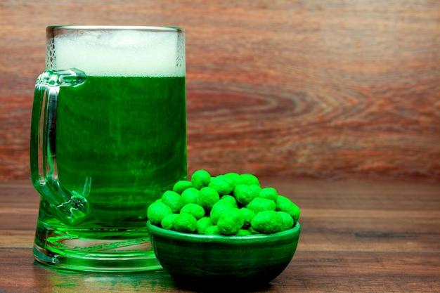 День святого патрика. зеленая стеклянная пинта пива и зеленые закуски печенье сладости на деревянный стол