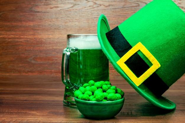 День святого патрика. зеленая стеклянная пинта пива, зеленые закуски, печенье, сладости и зеленая шляпа гнома на деревянном столе