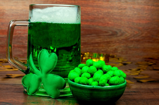성 패트릭의 날. 나무 테이블에 맥주, 녹색 스낵 쿠키 과자, 녹색 세 꽃잎 클로버와 금화의 녹색 유리 파인트