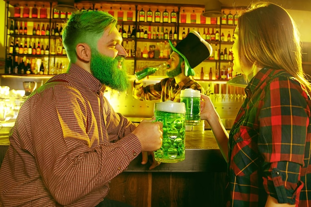 聖パトリックの日パーティー。幸せな友達が祝ってグリーンビールを飲んでいます。緑の帽子をかぶった若い男性と女性。パブのインテリア。