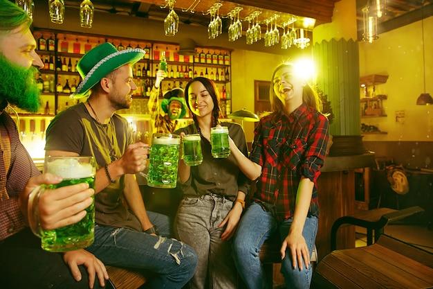 День святого патрика. счастливые друзья празднуют и пьют зеленое пиво. молодые мужчины и женщины в зеленых шляпах. интерьер паба.