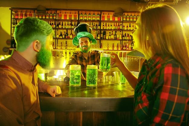 성 패트릭의 날 파티. 행복한 친구들이 축하하고 녹색 맥주를 마시고 있습니다.