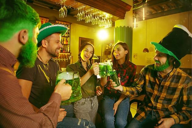 聖パトリックの日パーティー。幸せな友達は、緑色のビールを祝って飲んでいます。