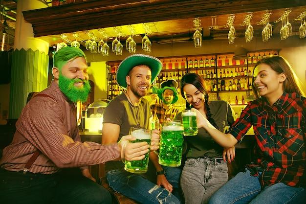 Festa di san patrizio. gli amici felici stanno festeggiando e bevendo birra verde.