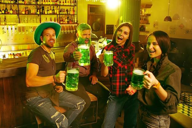聖パトリックの日パーティー。幸せな友達は、緑色のビールを祝って飲んでいます。緑の帽子をかぶっている若い男性と女性。パブのインテリア。
