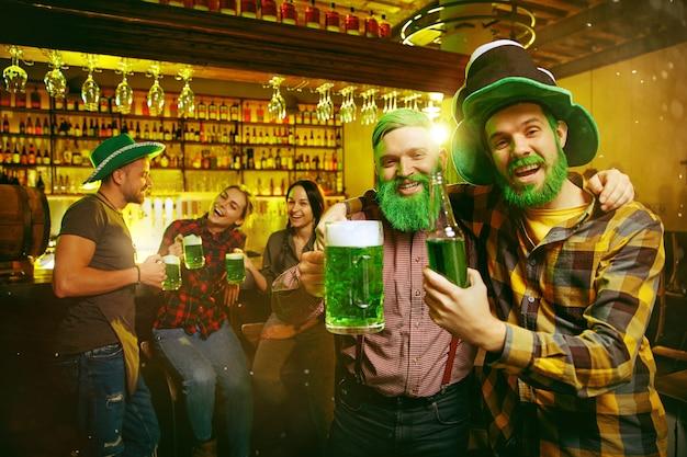Festa di san patrizio. amici felici festeggia e beve birra verde. giovani uomini e donne che indossano cappelli verdi. pub interno.