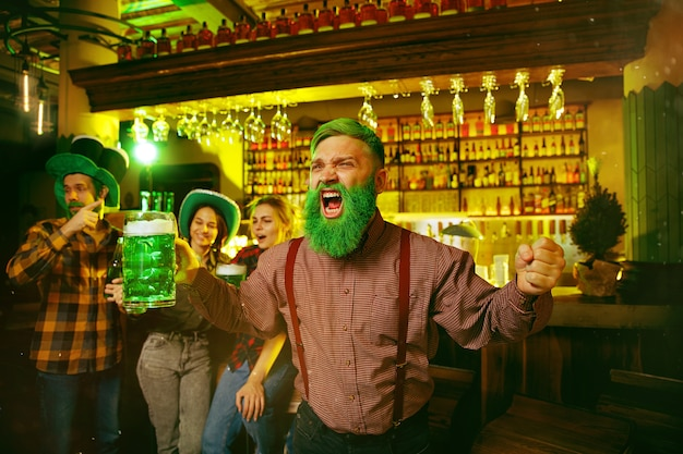 Saint patrick's day party. happy friends is celebrating and drinking green beer. young men and women wearing a green hats. pub interior.