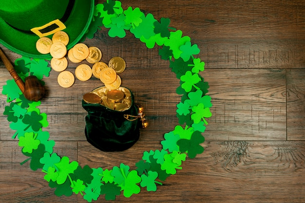 Saint patrick's day. small bag of leprechaun with gold coins lying on wooden background in circle shape of green three petal clovers