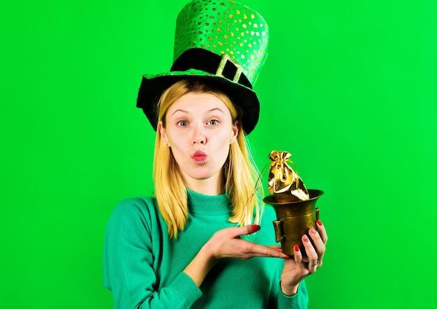 День святого патрика. ирландские традиции. женщина в шляпе лепрекона держит горшок с золотом. святой патрик.