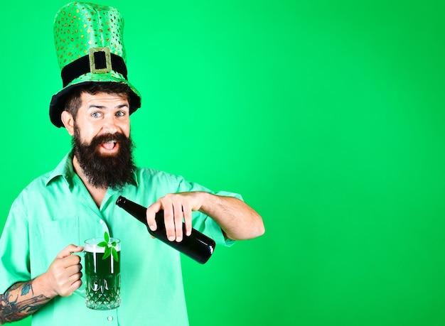 День святого патрика. улыбающийся бородатый мужчина в шляпе лепрекона наливает пиво в стакан.