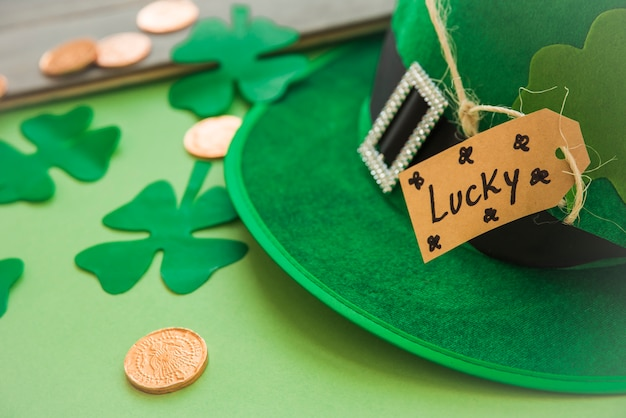 Saint patricks hat with tag near coins and decorative clovers