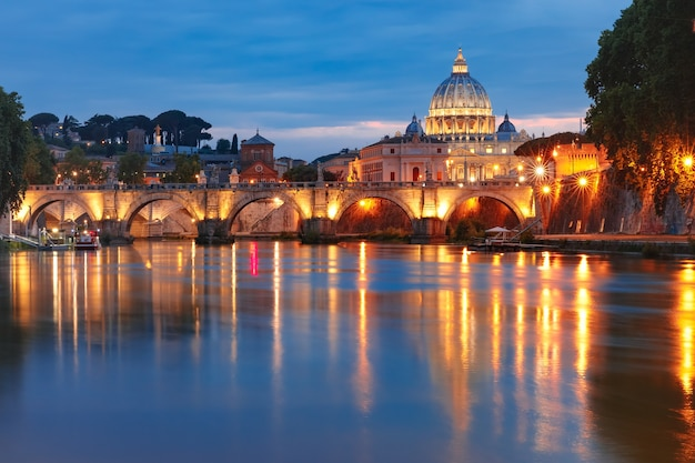 イタリア、ローマの朝のブルーアワーの間に、聖ペテロ大聖堂と聖天使がテヴェレ川に架かる橋。