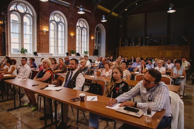 Санкт-петербург, июль 2019: бизнес-конференция компании blockchain, посвященная операциям с кибервалютой. спикер выступает во внутреннем зале перед своими партнерами и сотрудниками компании.