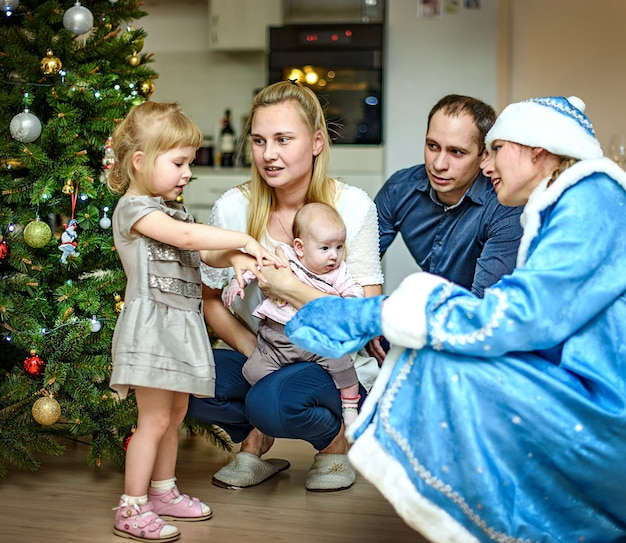 Saint petersburg, russia - 24 dec 2016: children's new year greetings. children playing with the snow maiden. greetings, gifts, dance around a christmas tree. family portraits.