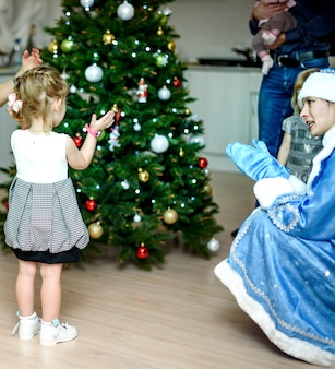 상트 페테르부르크, 러시아-2016 년 12 월 24 일 : 어린이 새해 인사. 눈 처녀와 노는 아이들. 인사말, 선물, 크리스마스 트리 주위에서 춤을 추십시오. 가족 초상화.