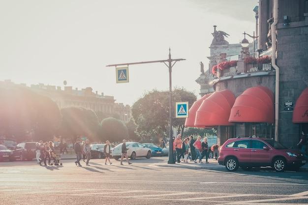 Санкт-петербург. россия. люди переходят улицу с движущимися машинами. эффект зернистости пленки, выборочный фокус. солнечные лучи в городе.