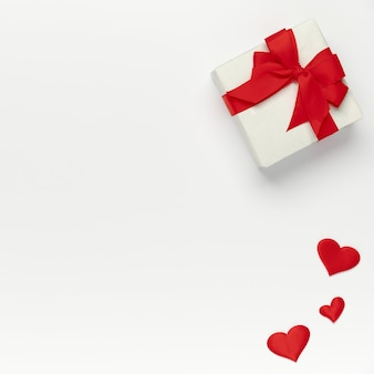 Saint valentine concept, top view of colored hearts and gift box on white isolated with place for text background