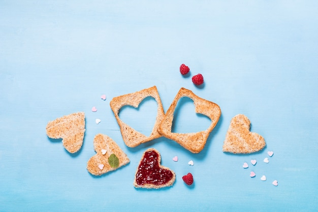 Saint valentine day background, heart shaped toast bread with raspberry jam on blue background, breakfast, romantic morning