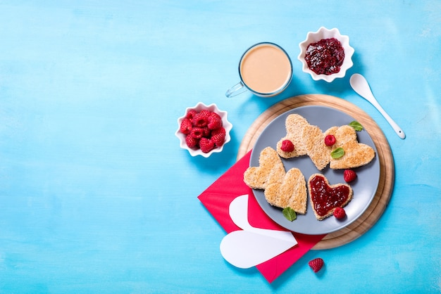 Saint valentine day background, heart shaped toast bread with raspberry jam and a cup of coffee on blue background