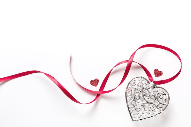 День святого валентина концепция, красивое серебряное сердце с маленькими красными сердечками с лентой