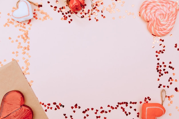 聖バレンタインデー。ピンクの背景に赤い手作りのフェルトハートとギフトボックスのフラットレイアレンジメント。