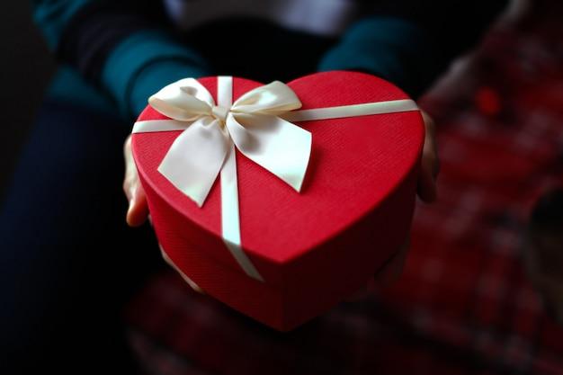 聖バレンタインの日の概念。装飾と彼の手で赤いハートプレゼントボックスを抱きかかえた