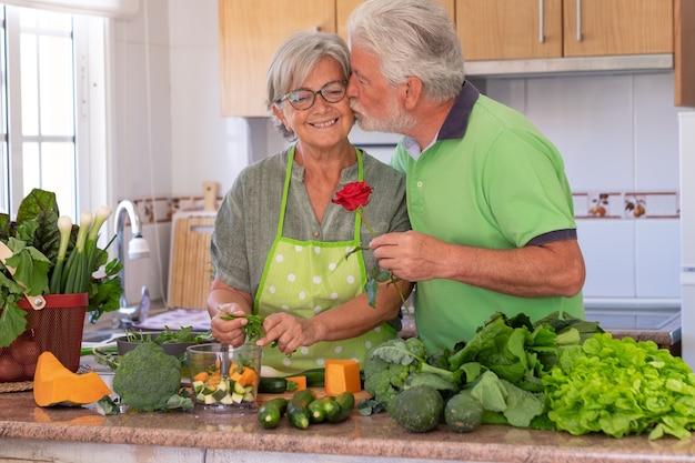 성 발렌타인 데이. 노인은 아내에게 키스하면서 장미를 선물합니다. 야채를 준비하는 동안 집 부엌에서 아름다운 노부부