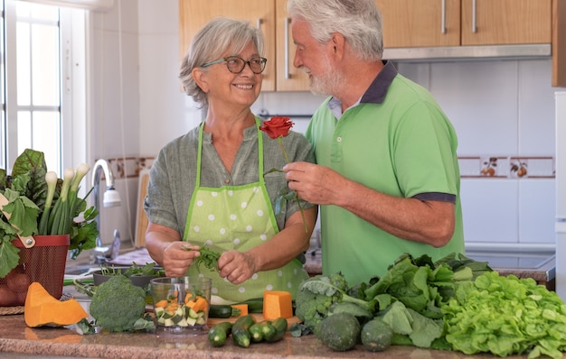 세인트 발렌타인 데이. 연로 한 남편이 아내에게 장미를 주면서 부드러운 사랑의 모습. 야채를 준비하는 동안 가정 부엌에서 아름 다운 수석 부부