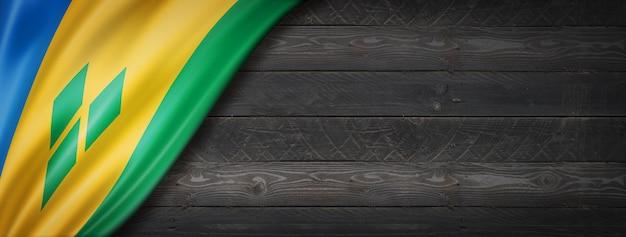 검은 나무 벽에 세인트 빈센트 그레나딘 플래그. 파노라마.