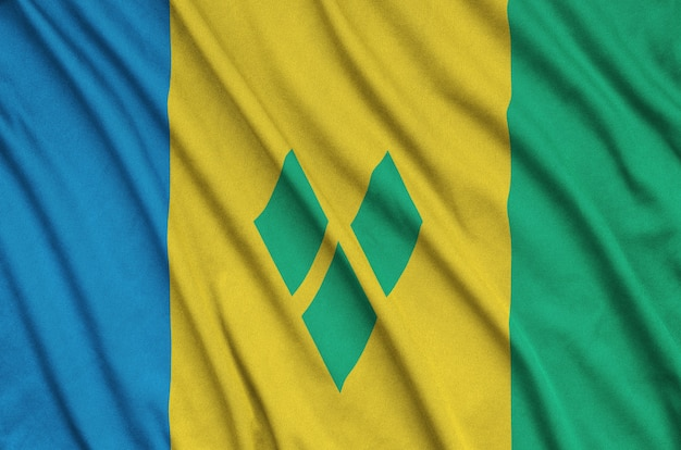 Saint vincent and the grenadines flag  is depicted on a sports cloth fabric with many folds.