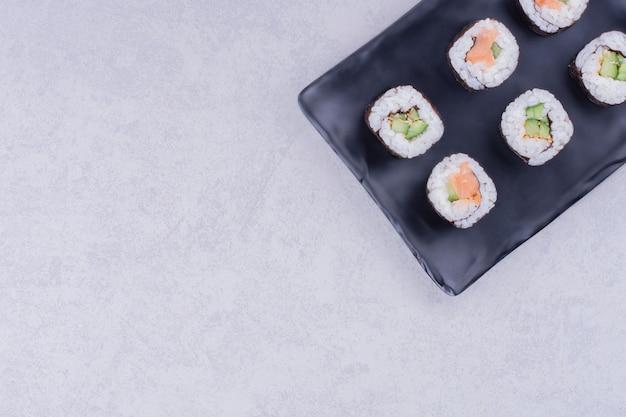 Il sake maki rotola in un piatto di ceramica nera
