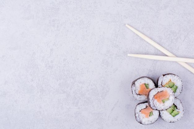 Sake maki rolls on grey background with chopsticks