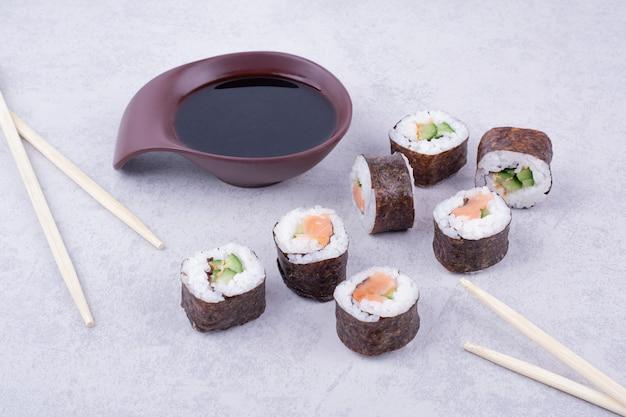 Il sake maki rotola su sfondo grigio con le bacchette