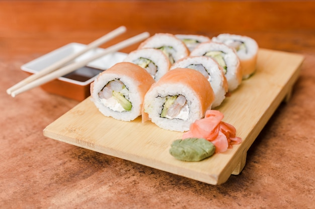 Sake roll with ginger, wasabi and soy sauce on a wooden table