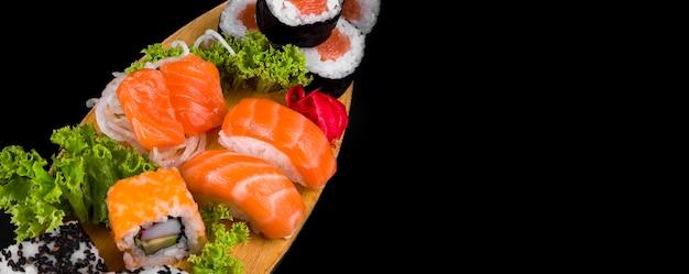 黒の背景に木の板にサケとホソマキ。黒に寿司をセット