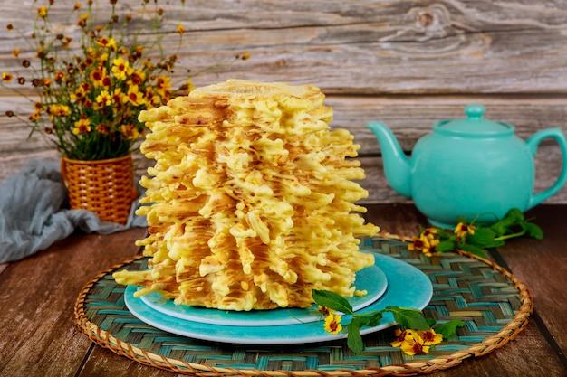 ティーポットと花が付いているリトアニアのsakotisケーキ。