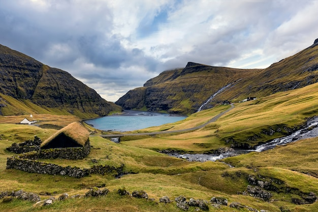 Saksun village and sandy shore of the lagoon with an azure lake and dramatic clouds in faroe islands