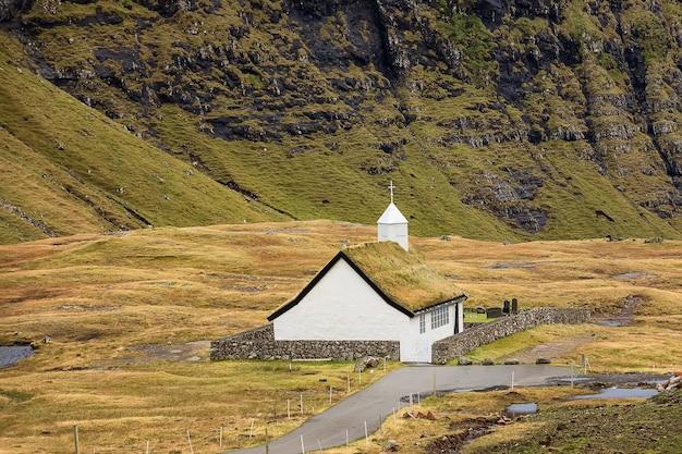 Церковь саксунар киркья и горы возле деревни саксун, фарерские острова, дания