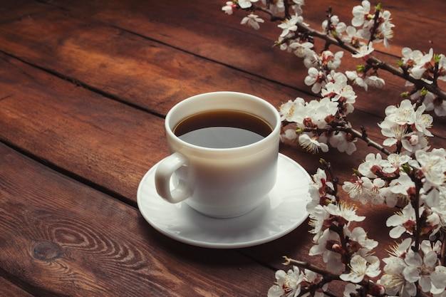 花と桜の枝と暗い木の表面にブラックコーヒーと白いカップ。春のコンセプト