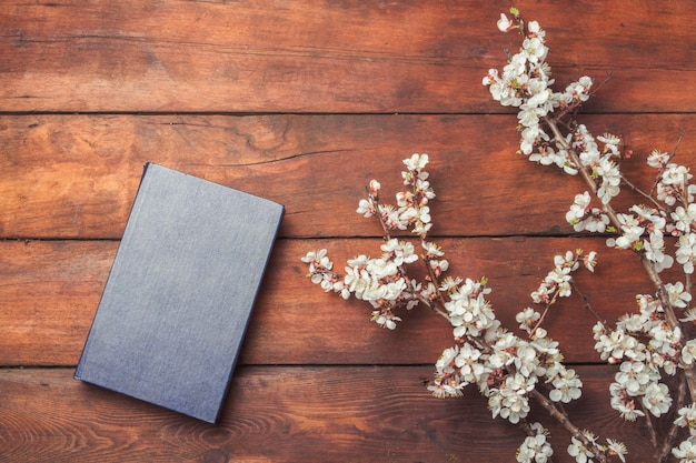 Sakura branches with flowers and a book on a dark wooden surface