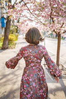 さくらは街の通りの木に花を咲かせて枝分かれしています。桜が咲く通りで回転する幸せな女の女の子。さくらの花。