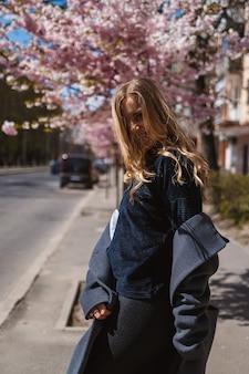 街の通りの木に花が咲く桜の枝。灰色のパレットで幸せな女性の女の子は、咲く桜と路地を歩きます。屋外でゴージャスな派手な女の子。桜が咲いています。