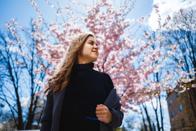 街の通りの木に花が咲く桜の枝。桜が咲く通りに立つスタイリッシュな女の女の子。屋外で現代のファッショナブルな女の子。桜。