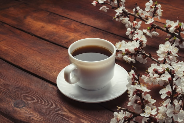 Sakura branches with flowers and a white cup with a black coffee on a dark wooden surface. concept of spring