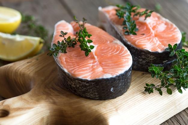 ボード上の新鮮で新鮮なサーモンステーキとスパイス。生sal赤魚。料理サーモン、シーフード。健康食品のコンセプト。サーモンとスパイス