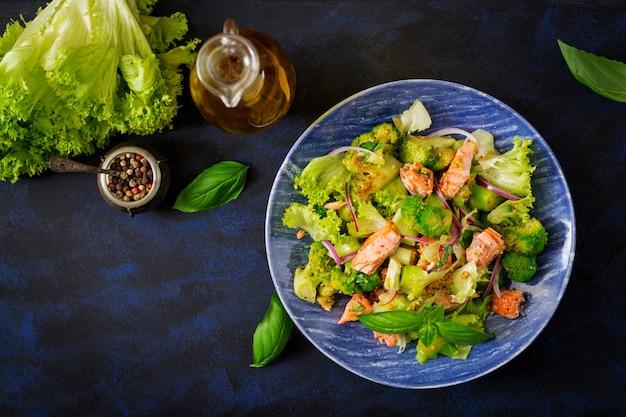 魚のsal煮、ブロッコリー、レタス、ドレッシングのサラダ。魚のメニュー。食事メニュー。シーフード-サーモン。上面図