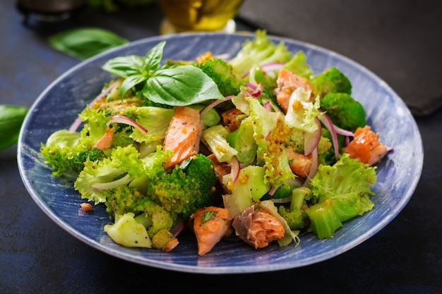 魚のsal煮、ブロッコリー、レタス、ドレッシングのサラダ。魚のメニュー。食事メニュー。シーフード-サーモン。