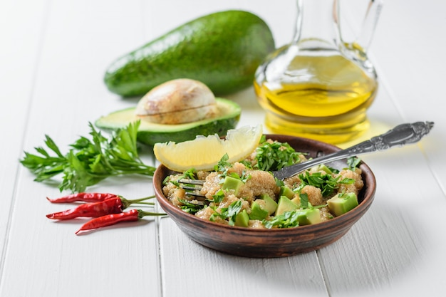 Salad of amaranth seeds, avocado and parsley with olive oil on a table.